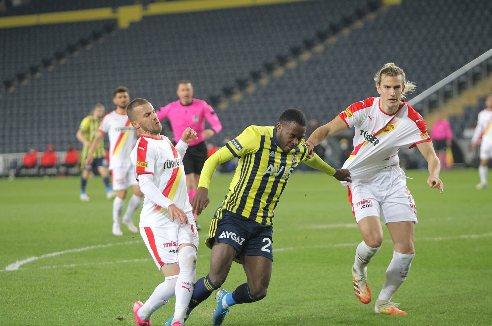 A player from Fenerbahçe (C) battles with two from Göztepe during their Süper Lig match, a 1-0  Göztepe win at Ülker Stadium in Istanbul, Turkey, Feb. 21, 2021. (DHA Photo)