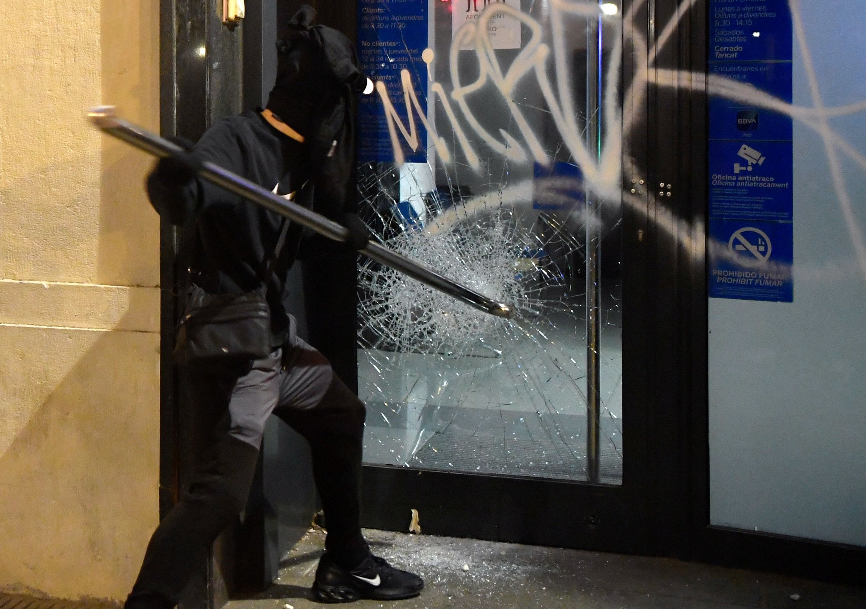 A protester breaks the glass of a bank branch's door during clashes with Catalan regional police forces Mossos d'Esquadra after a demonstration against the imprisonment of Spanish rapper Pablo Hasel in Barcelona on Feb. 19, 2021. (AFP Photo)