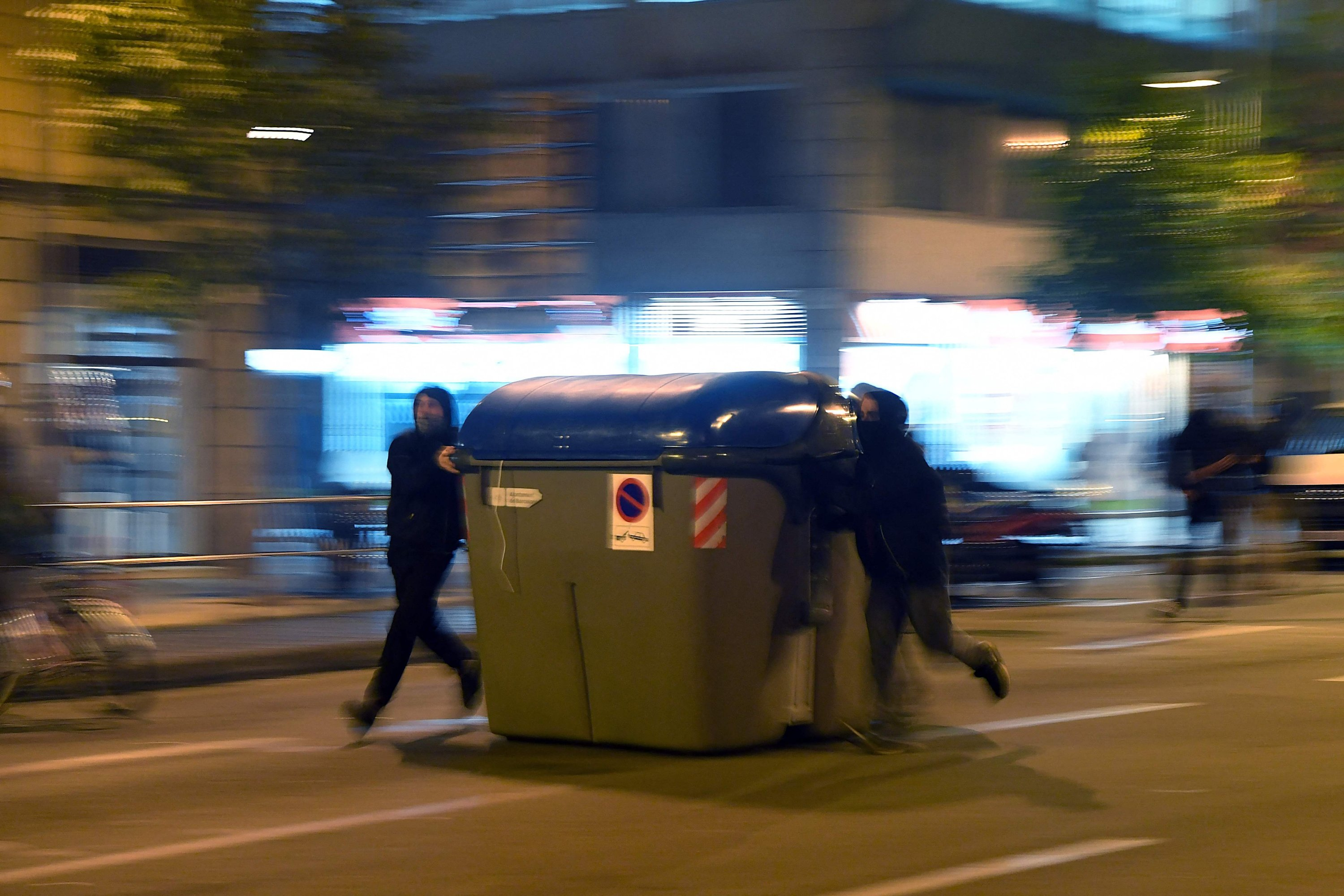 Protesters push a trash container during clashes with Catalan regional police forces Mossos d'Esquadra after a demonstration against the imprisonment of Spanish rapper Pablo Hasel in Barcelona on Feb. 19, 2021. (AFP Photo)