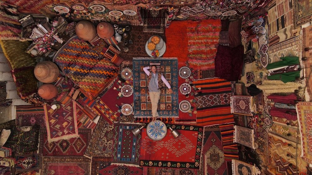 "Richard Quest of CNN's ""Quest's World of Wonder"" lays among Turkish carpets at Cappadocia. (Courtesy of Warner Media)"
