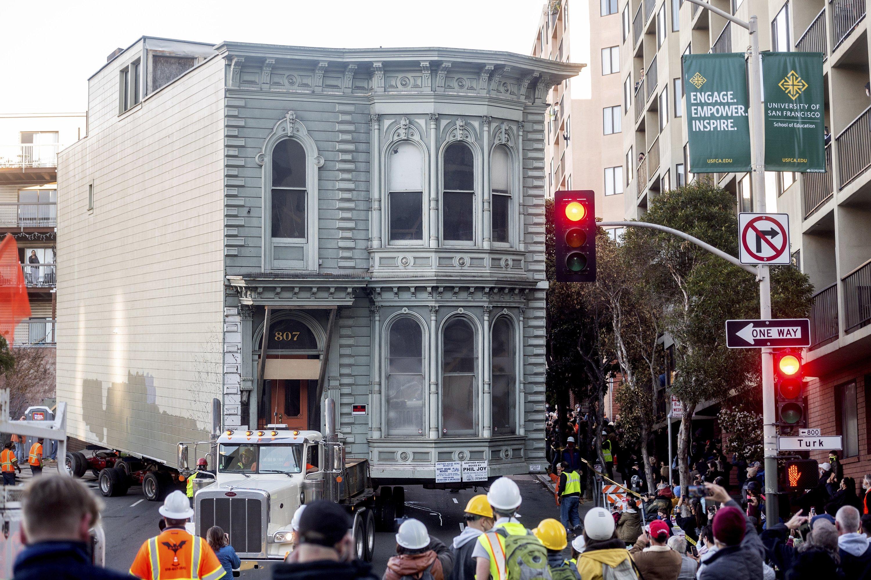 Crowds watch as a truck pulls a Victorian home through San Francisco on Feb. 21, 2021. (AP Photo)