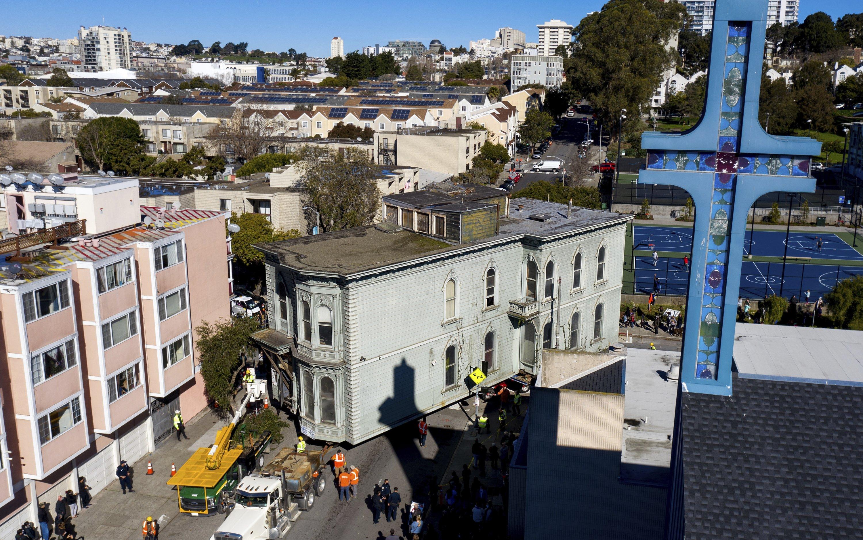 A truck pulls a Victorian home through San Francisco on Feb. 21, 2021. (AP Photo)