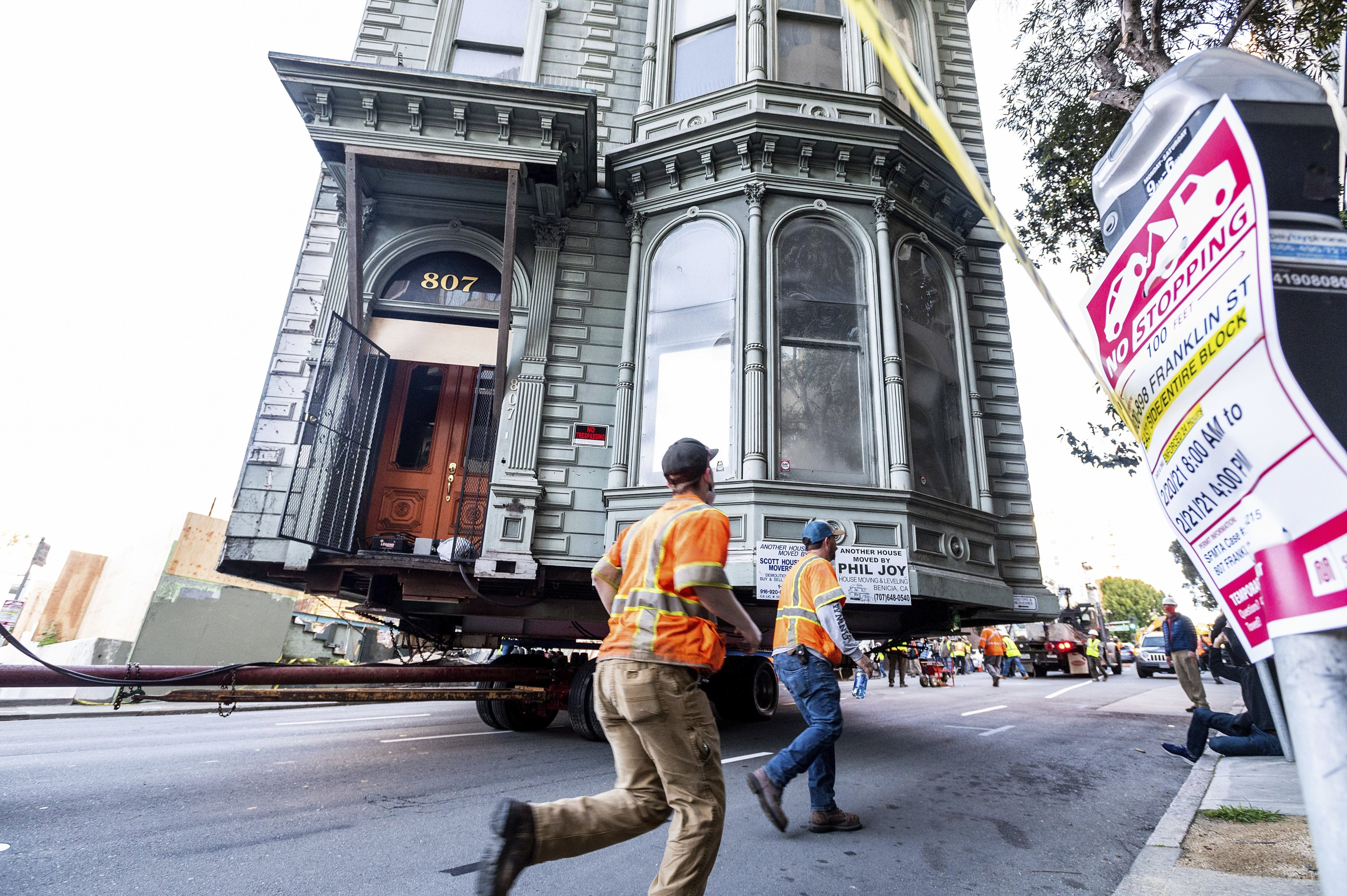 Workers pass a Victorian home as a truck pulls it through San Francisco on Feb. 21, 2021. (AP Photo)