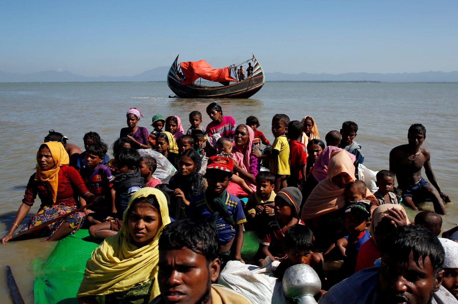 Rohingya refugees sit on a makeshift boat as they get interrogated by the Border Guard Bangladesh after crossing the Bangladesh-Myanmar border, at Shah Porir Dwip near Cox's Bazar, Bangladesh November 9, 2017. (Reuters Photo)