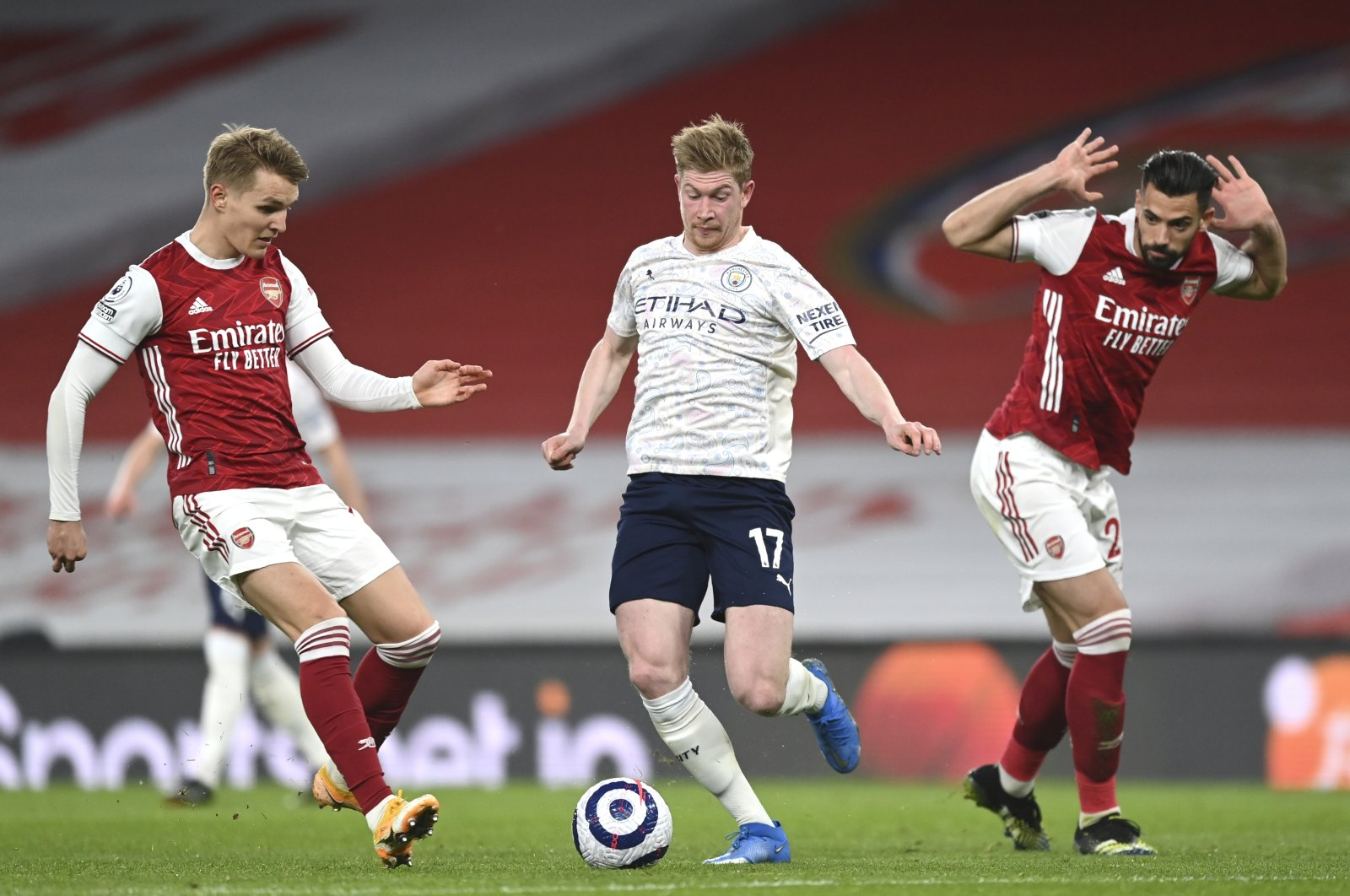 Arsenal's Martin Odegaard (L) and Manchester City's Kevin De Bruyne challenge for the ball during a Premier League match at the Emirates, London, England, Sunday, Feb. 21, 2021. (AP Photo)