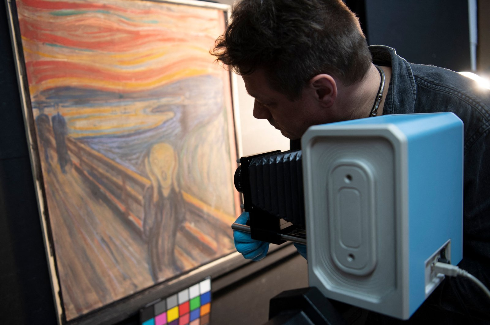 """In this undated handout image, a curator at the National Museum of Norway uses an infrared scanner in the quest to reveal the author of hidden graffiti on Edvard Munch's original painting of """"The Scream"""" in Oslo. (AFP PHOTO)"""