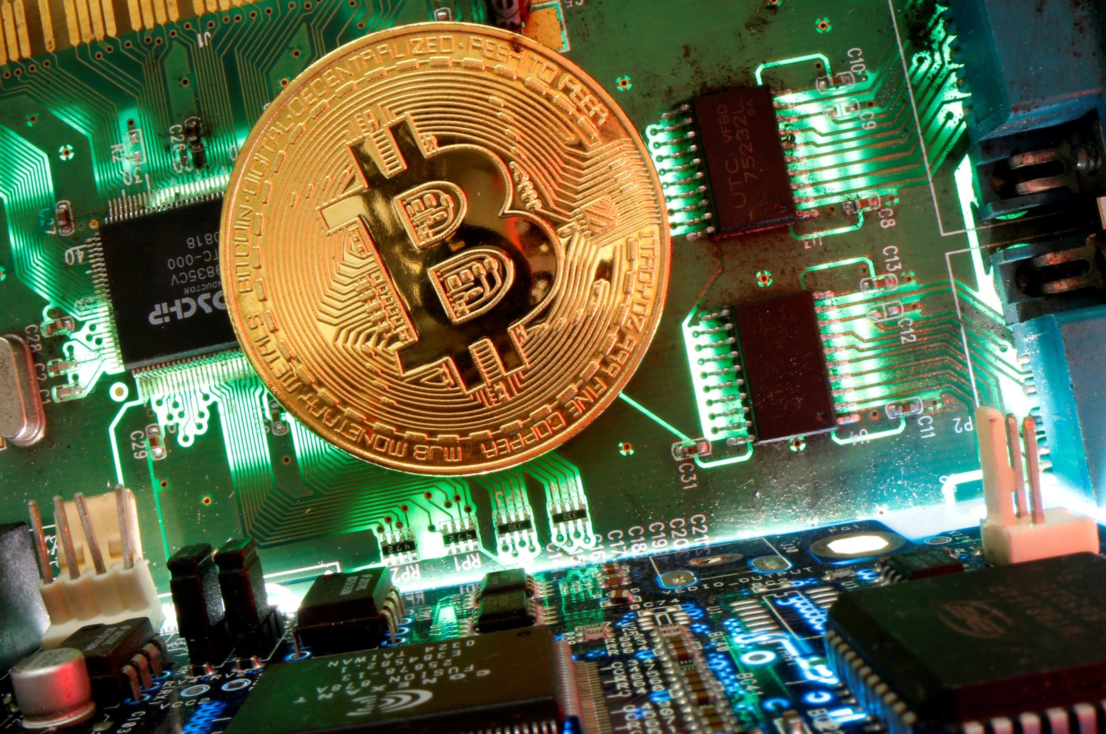 A representation of the virtual currency Bitcoin is seen on a motherboard in this illustration, April 24, 2020 (Reuters)