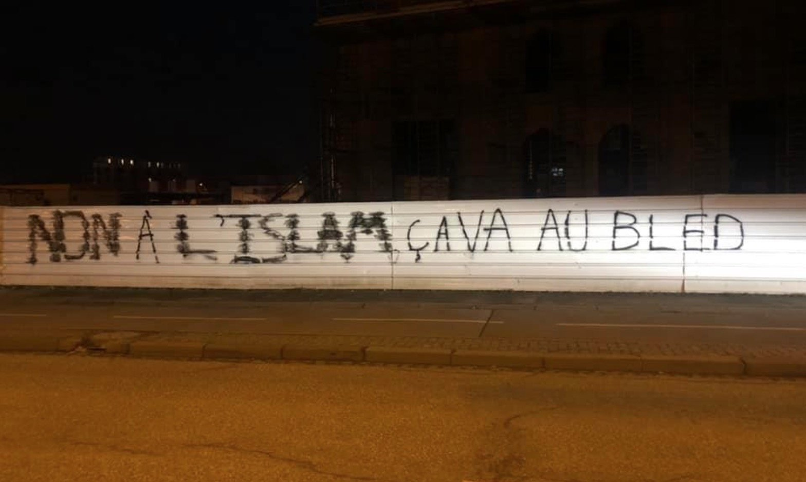 "Words in French that translate to ""No to Islam, go back to your village"" are seen sprayed across the fence on the site of the Eyyub Sultan Mosque in France's Strasbourg on Feb. 23, 2021. (Photo taken from Twitter)"