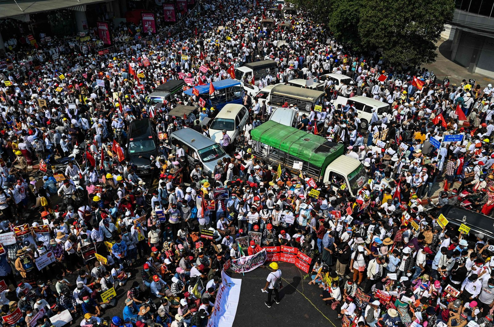 Protesters mass around vehicles as they block roads during a demonstration against the military coup in Yangon on Feb. 22, 2021. (AFP Photo)