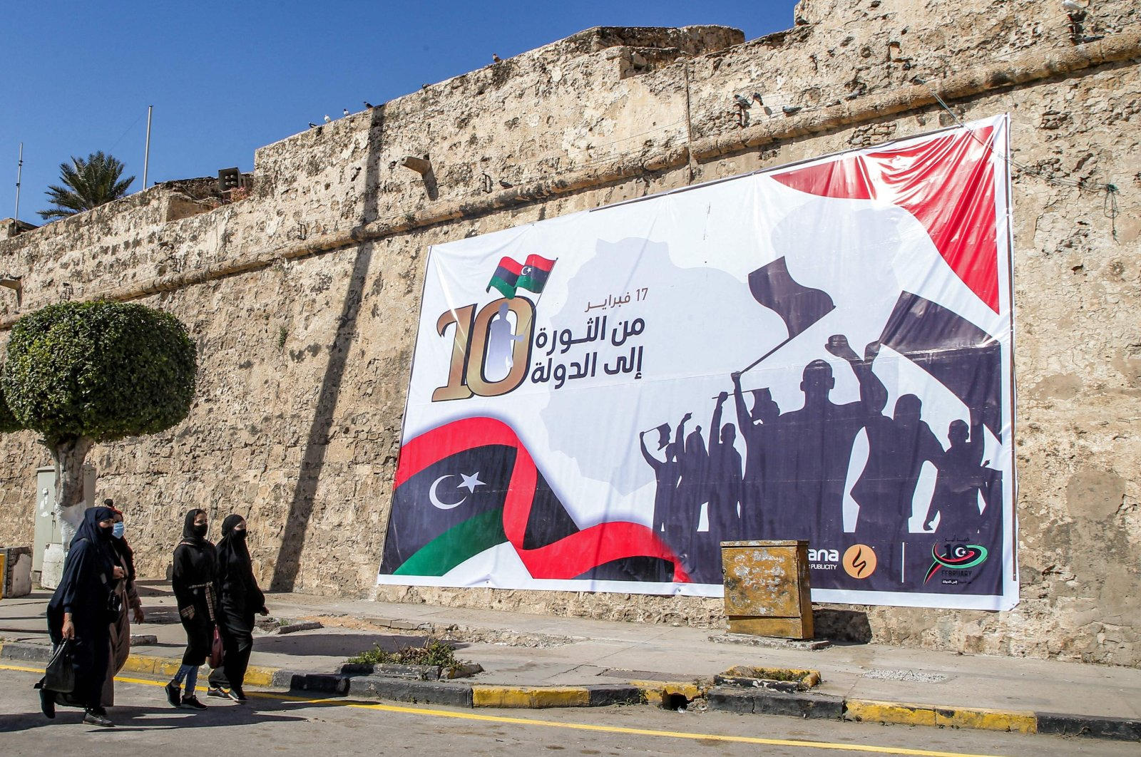 Women walk past a banner hanging on the walls of the Red Castle in the center of Libya's capital Tripoli on Feb. 16, 2021. (AFP Photo)