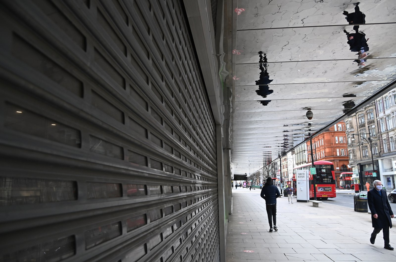 People walked past a closed shopfront on Oxford Street, London, Britain, Feb. 12, 2021. (Reuters Photo)