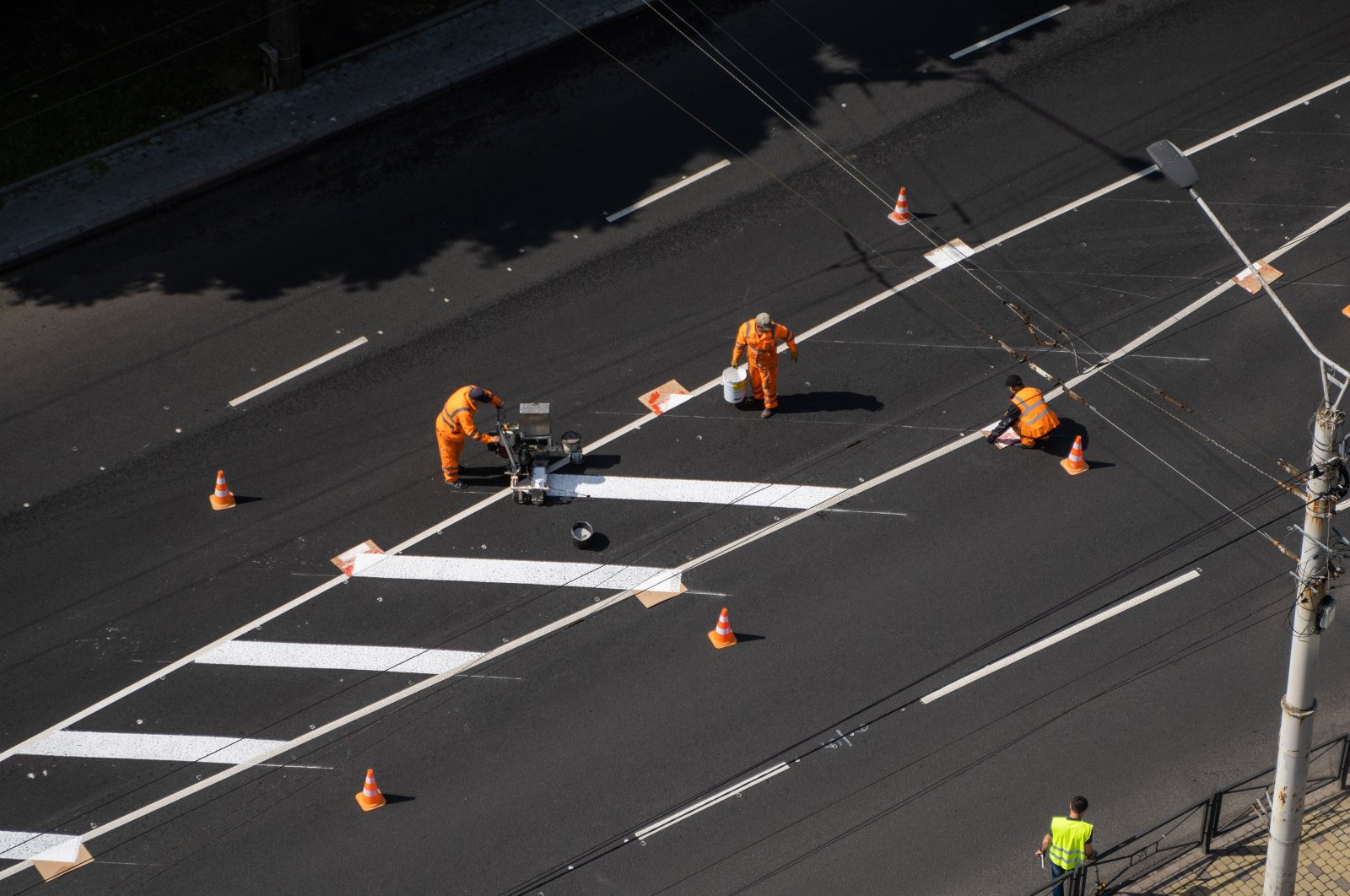 Road workers paint white lines on the road during road construction, Kyiv, Ukraine, May 25, 2020. (Shutterstock Photo)