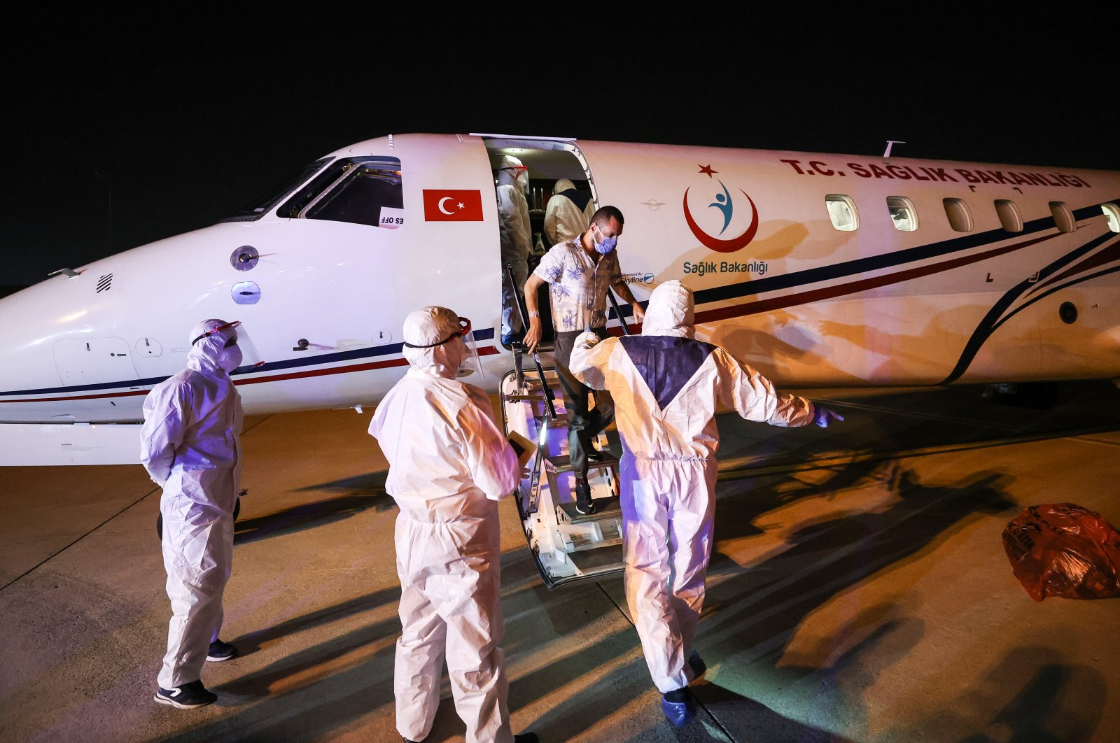 Health care workers accompany a patient as he disembarks an air ambulance, in Istanbul, Turkey, Feb. 23, 2021. (AA Photo)