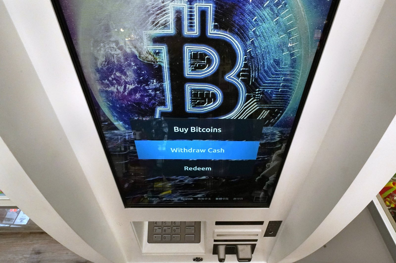 The Bitcoin logo appears on the display screen of a cryptocurrency ATM at the Smoker's Choice store in Salem, New Hampshire, U.S.,Feb. 9, 2021. (AP Photo)