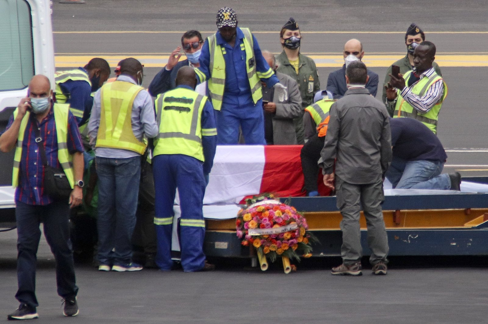 The coffins of Italian ambassador to Congo Luca Attanasio and Carabinieri officer Vittorio Iacovacci, draped with the Italian flag, are prepared to be loaded onto an airplane for repatriation to Italy, at the airport in Goma, North Kivu province, Congo, Feb. 23, 2021. (AP Photo)