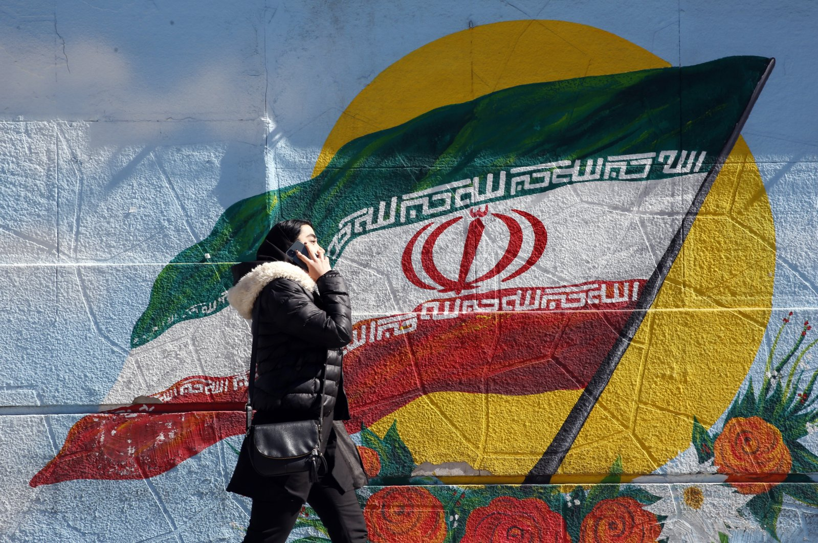 An Iranian woman speaks over the phone while walking next to a wall painting of the Iranian national flag in Tehran, Iran, Feb. 23, 2021. (EPA Photo)