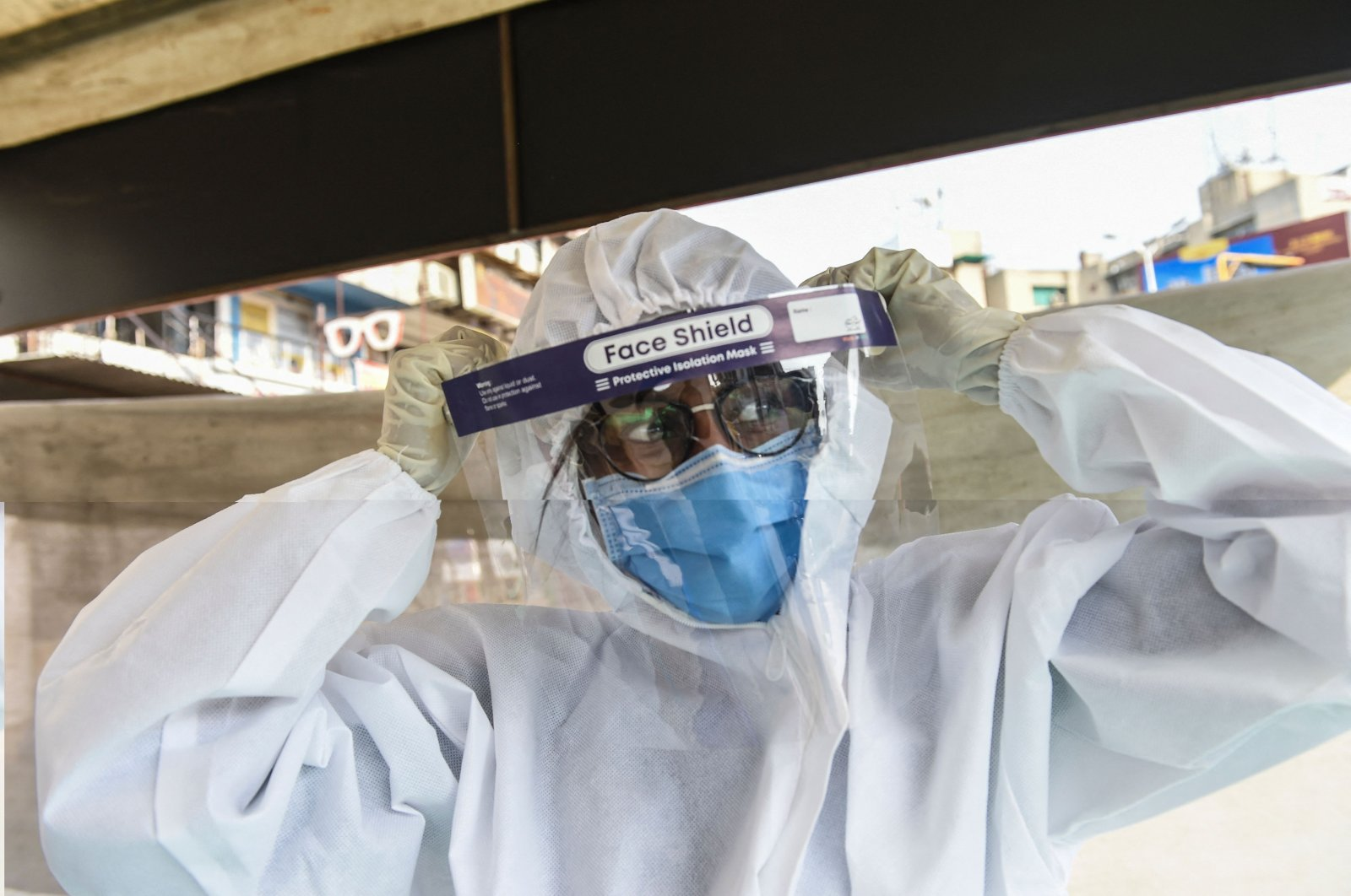 A health worker wears a Personal Protective Equipment (PPE) suit before collecting swab samples from people to test for the coronavirus, Ahmedabad, India, Feb. 22, 2021. (AFP Photo)