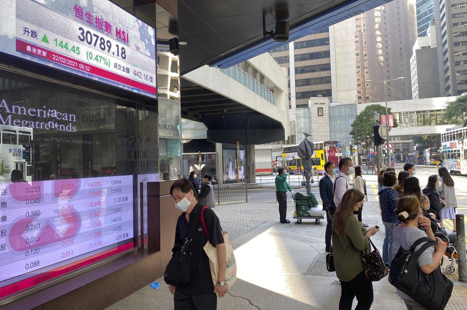 People walk past a bank's electronic board showing the Hong Kong share index in Hong Kong Monday, Feb. 22, 2021. (AP Photo)