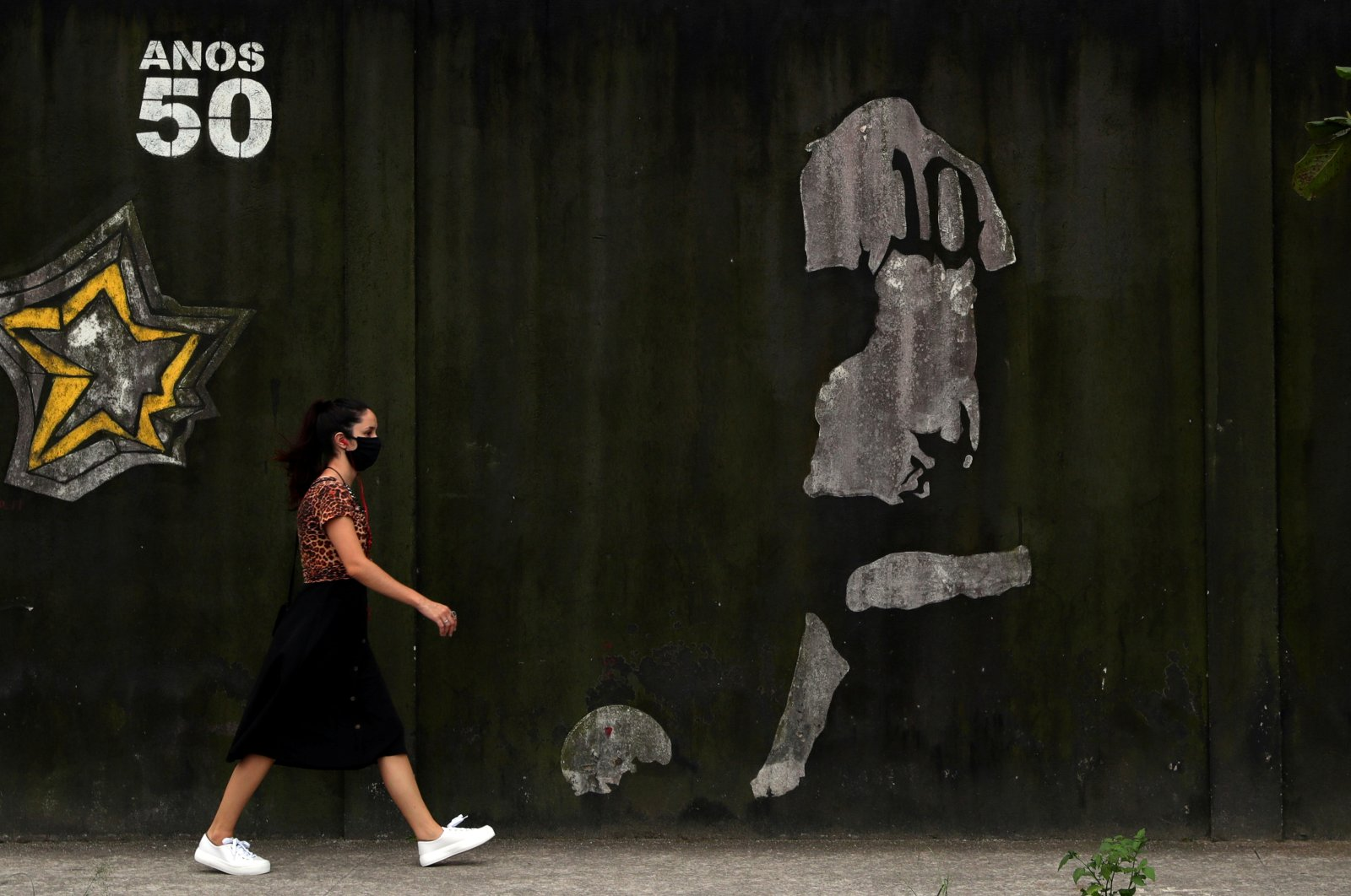 A woman walks by a mural depicting Brazilian soccer legend Pele in his iconic number 10 shirt, in Santos, Brazil, Oct. 20, 2020. (Reuters Photo)