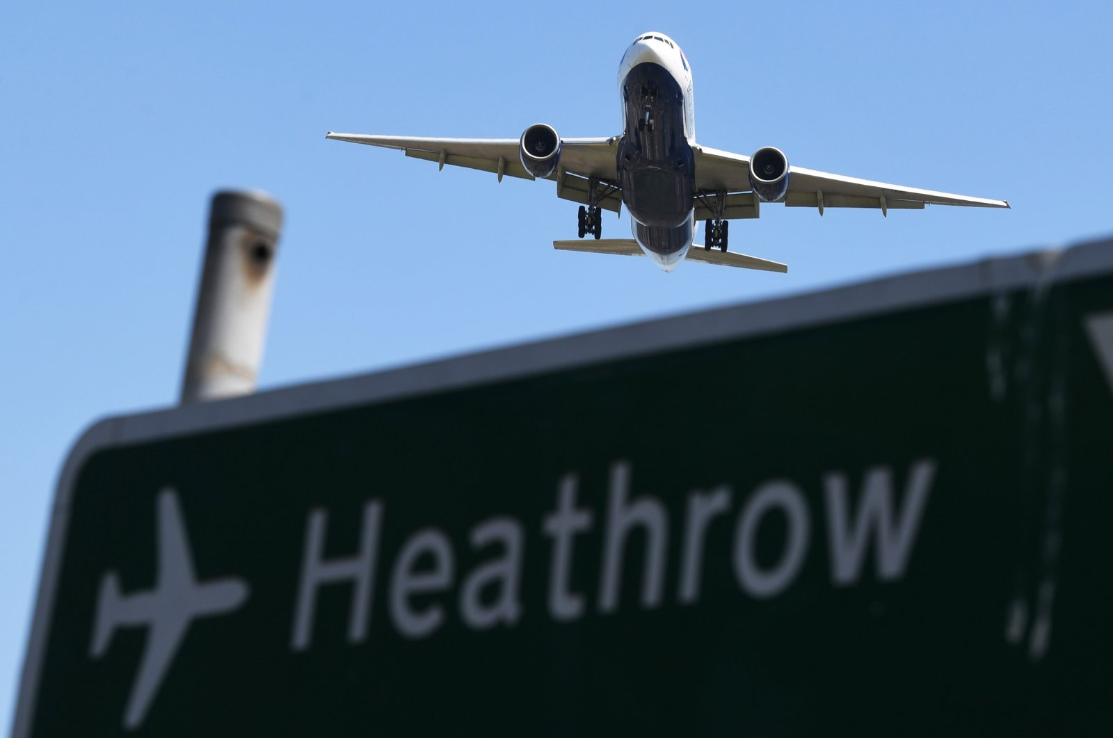 A plane passes a sign as it comes in to land at Heathrow Airport in Hounslow, Britain, June 25, 2018. (EPA Photo)