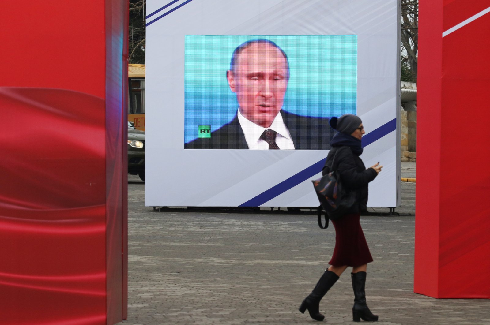 A woman walks past a screen showing Russian President Vladimir Putin during celebrations of the Defender of the Fatherland Day in Sevastopol, Crimea, Feb. 23, 2021. (REUTERS Photo)