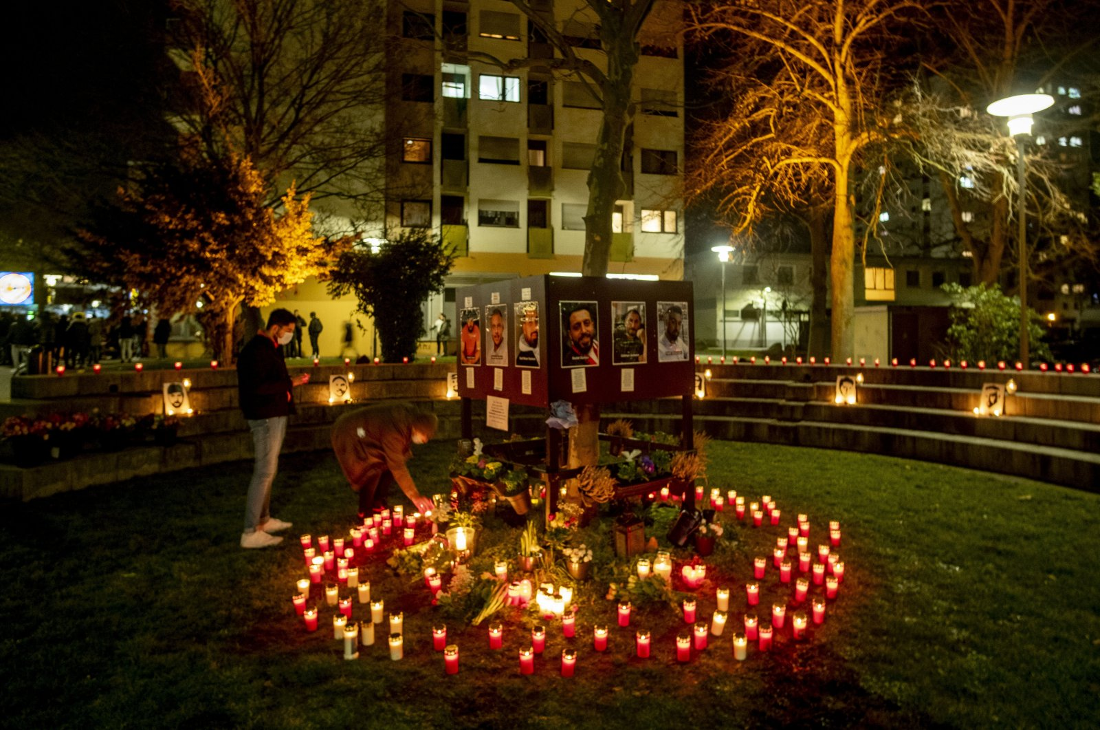 People light candles in front of a kiosk where several were killed in a racist attack one year ago in Hanau, Germany, Feb. 19, 2021. (AP Photo)
