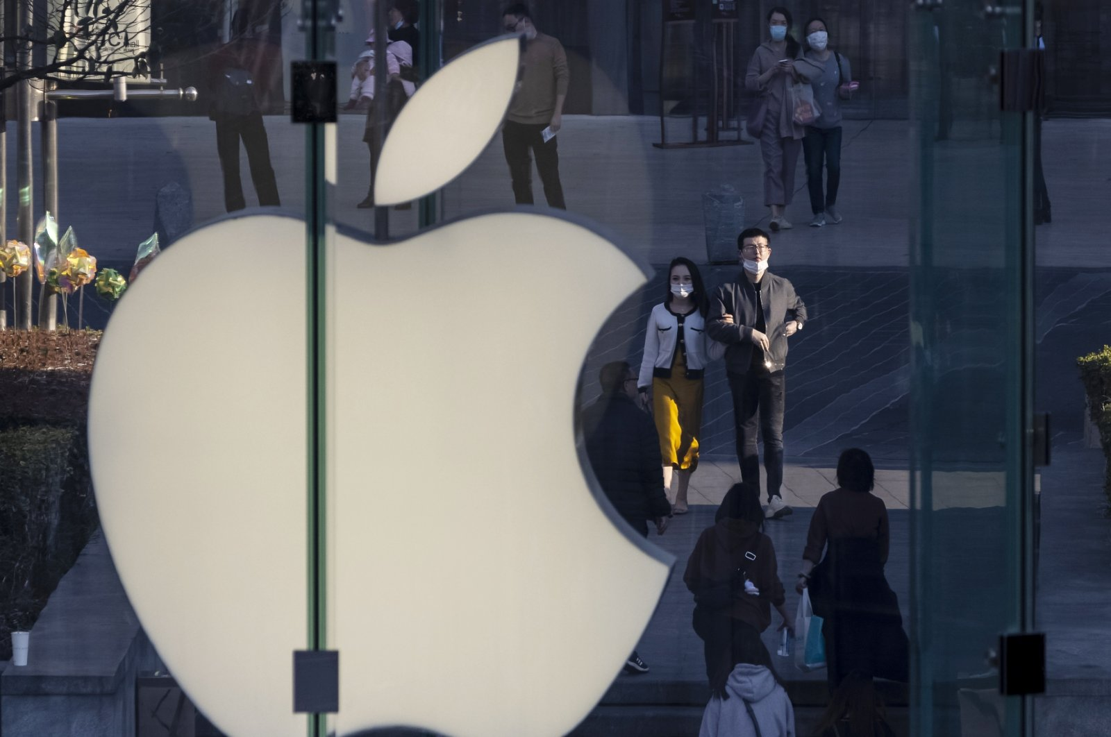 People walk next to the Apple logo in the financial district of Shanghai, China, Feb. 21, 2021. (EPA Photo)
