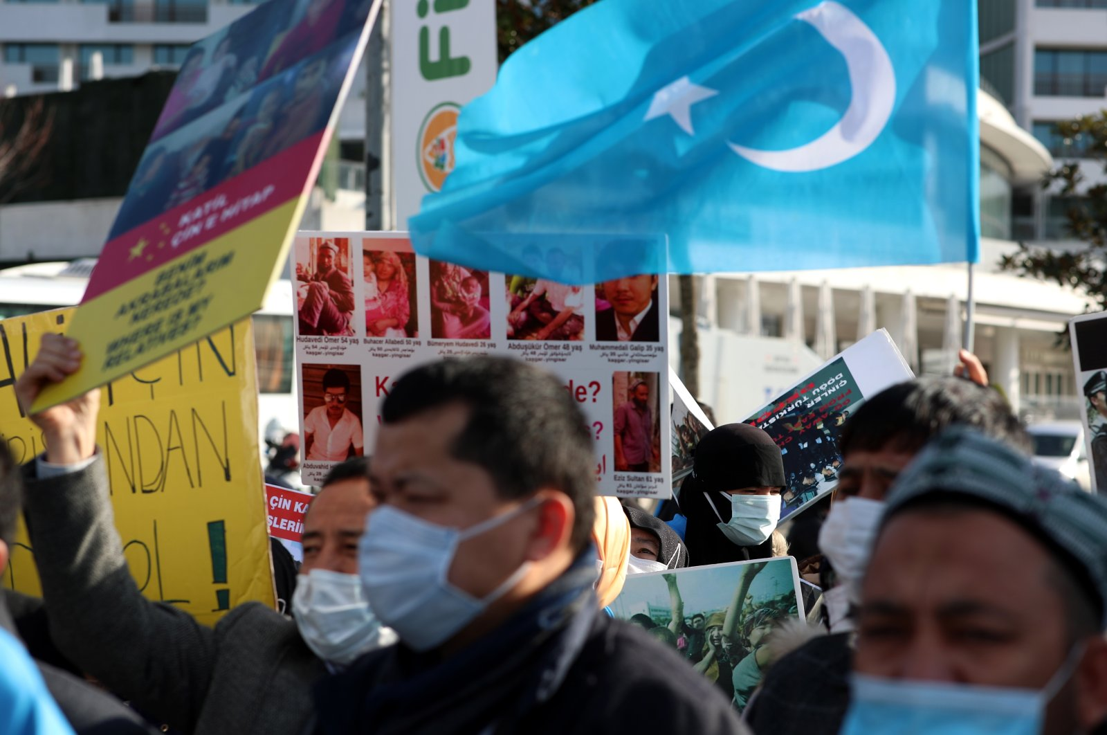Uyghur protestors who have not heard from their families living in Xinjiang hold placards and Uyghur flags during a protest against China, near the Chinese consulate-general in Istanbul, Turkey, Feb. 9, 2021 (EPA Photo)