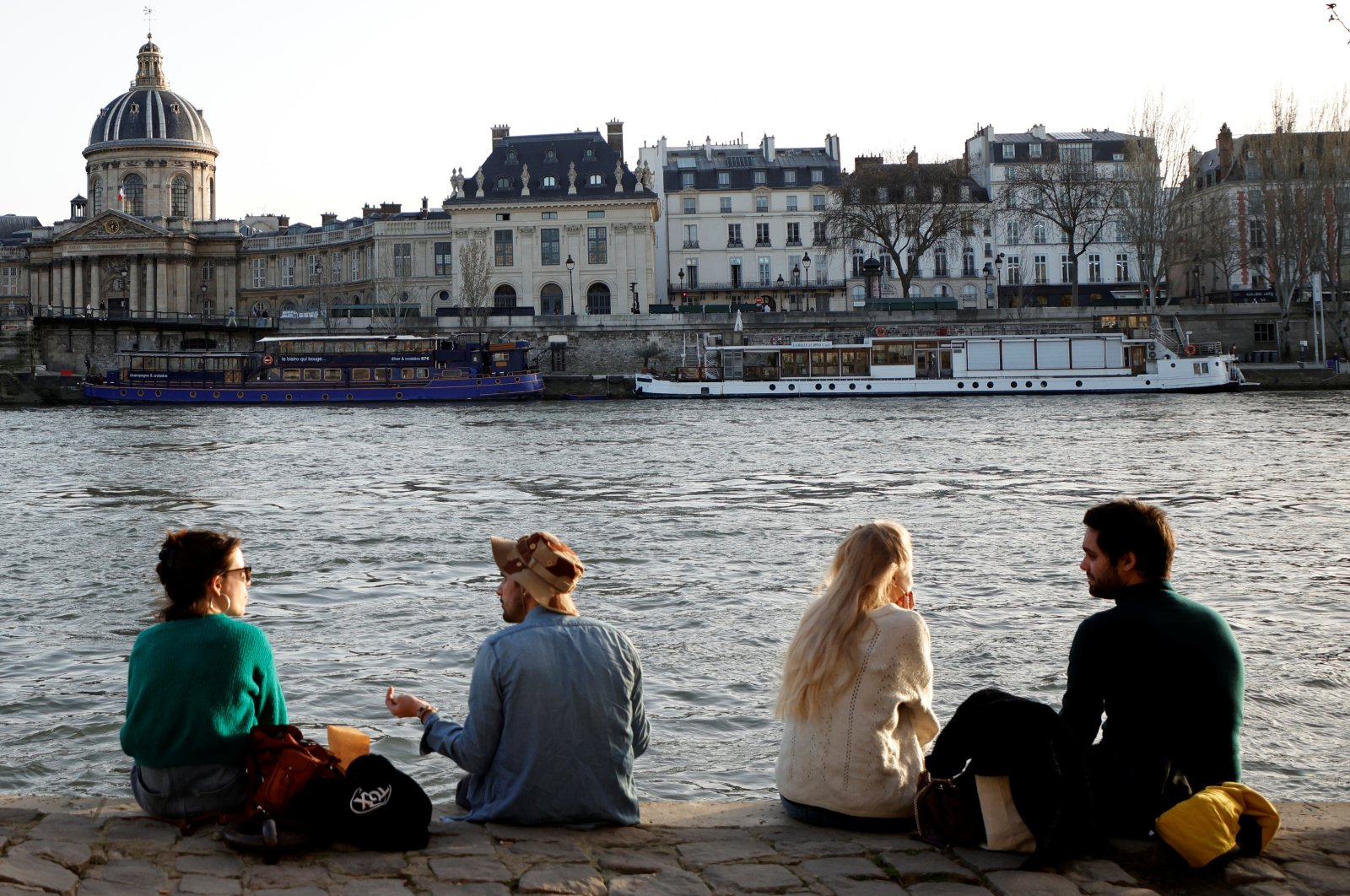 People enjoy sunny warm weather while sitting on the banks of the River Seine amid the coronavirus disease (COVID-19) outbreak in Paris, France, Feb. 24, 2021. (Reuters Photo)