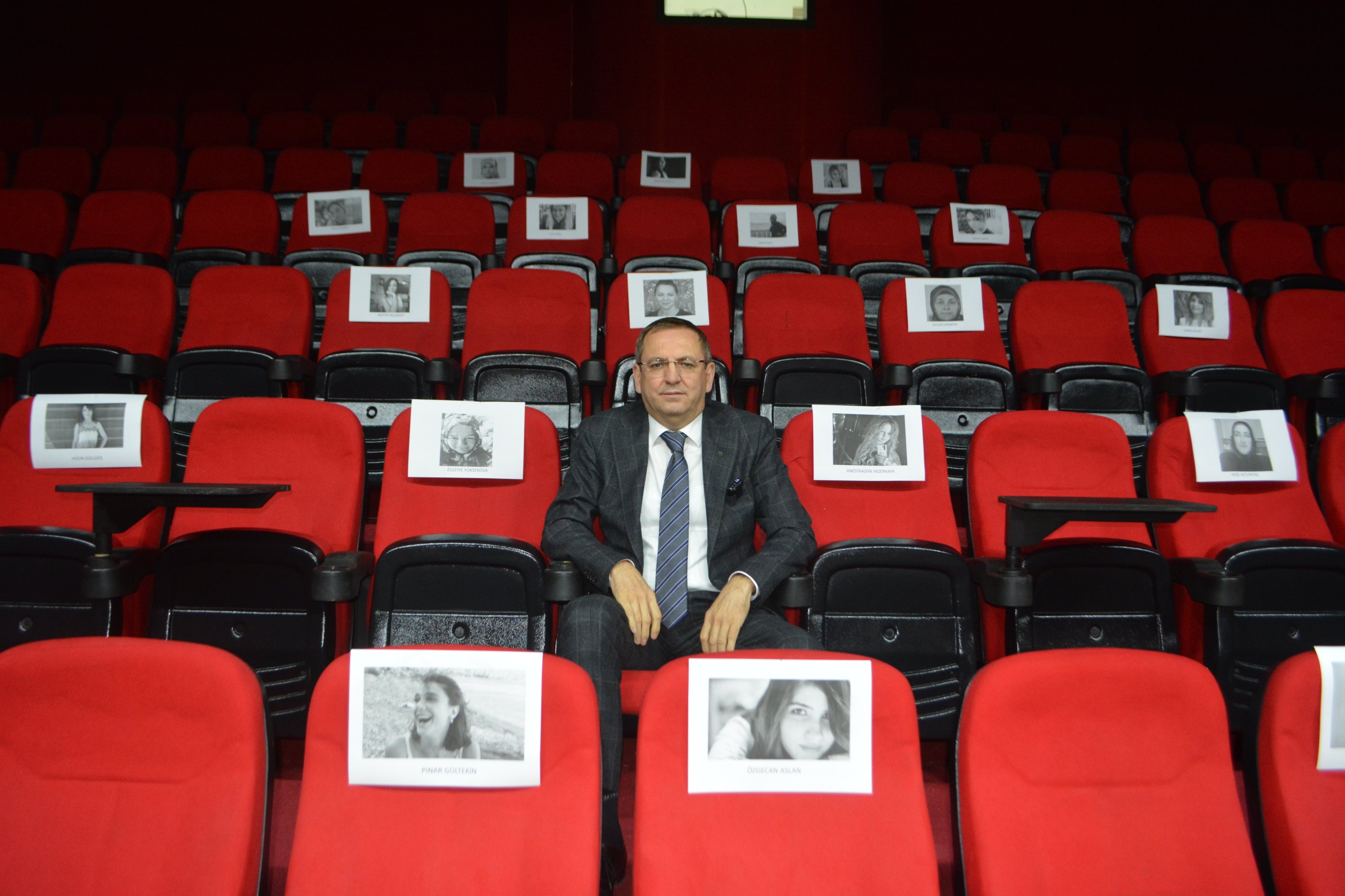 Ayvalık Mayor Mesut Ergin sits at the Vural Theater surrounded by pictures of female victims that lost their lives in homicides, Balıkesir, western Turkey, Feb. 24, 2021. (AA Photo)