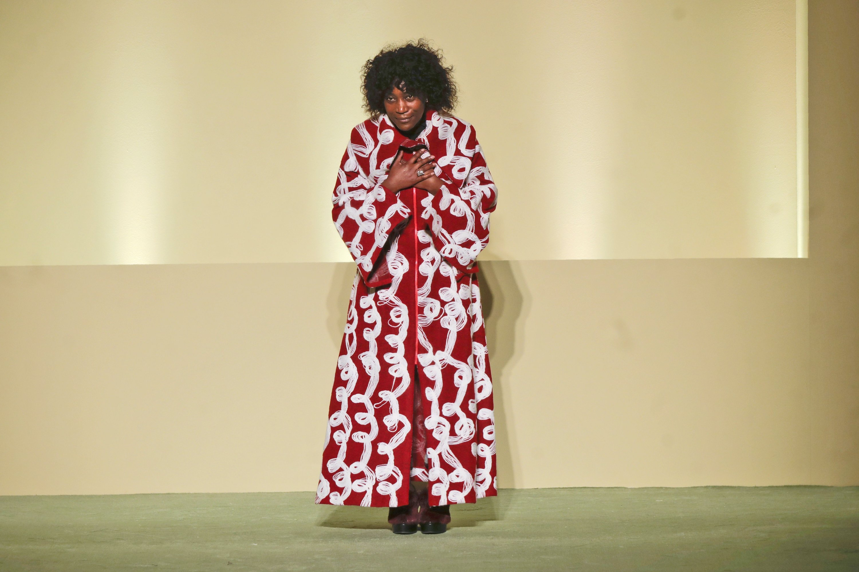Fashion designer Fabiola Manirakiza stands on the catwalk at the end of the collective Black Lives Matter Fall / Winter 2021/22 fashion show, which is being presented in Milan, Italy, February 17, 2021. (AP Photo)