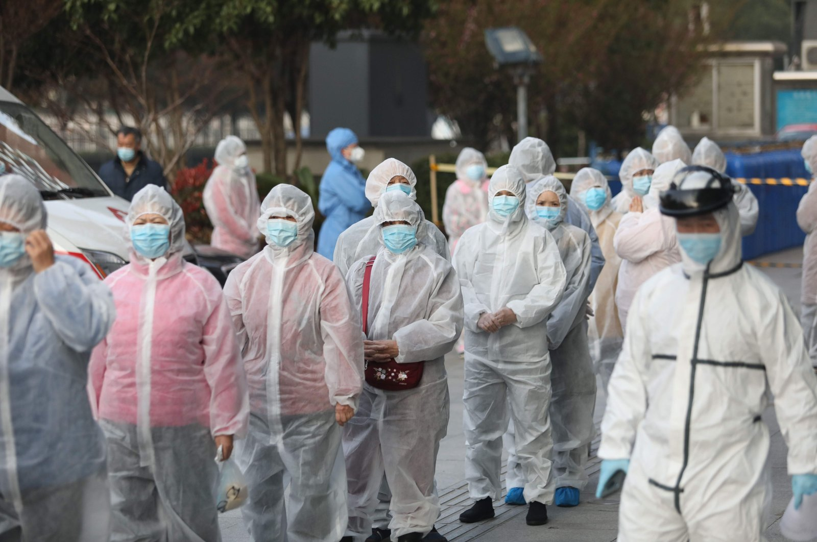 Patients who recovered from COVID-19 wear protective clothing as they line up to be tested again at a hospital in Wuhan, Hubei province, central China, March 14, 2020. (AFP Photo)