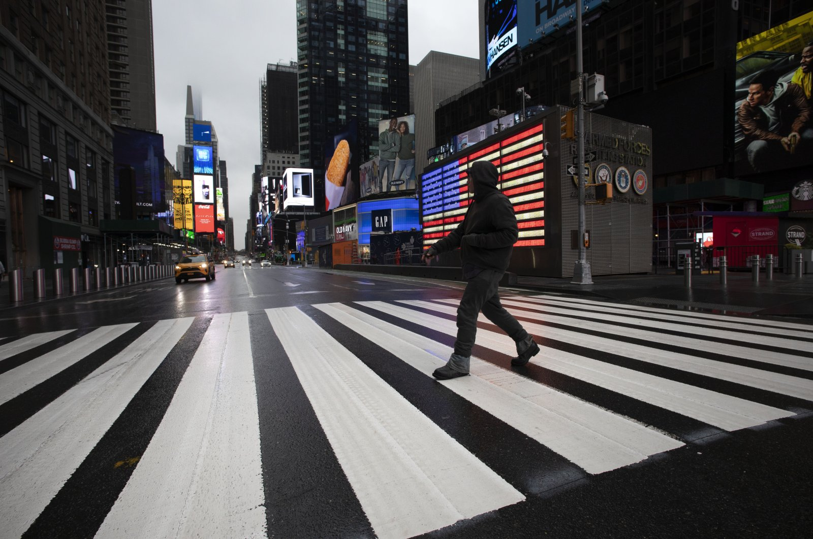 A man crosses the street in a nearly empty Times Square, which is usually very crowded on a weekday morning in New York, March 23, 2020. (AP Photo)