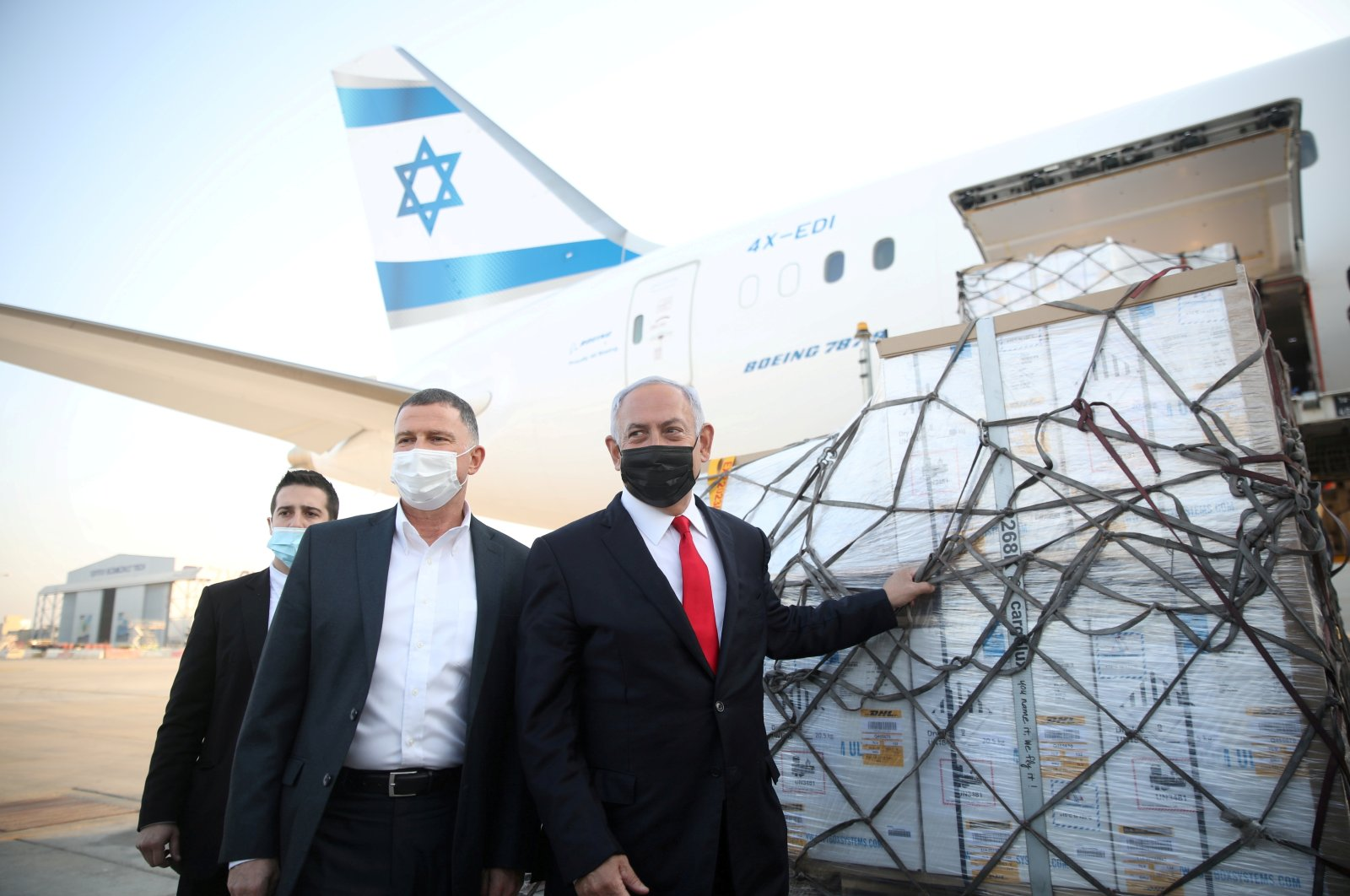 Israeli Health Minister Yuli Edelstein (C) and Prime Minister Benjamin Netanyahu (R) attend the arrival of a plane with a shipment of Pfizer-BioNTech COVID-19 vaccines, at Ben Gurion airport, near the city of Lod, Israel, Jan. 10, 2021. (Reuters Photo)