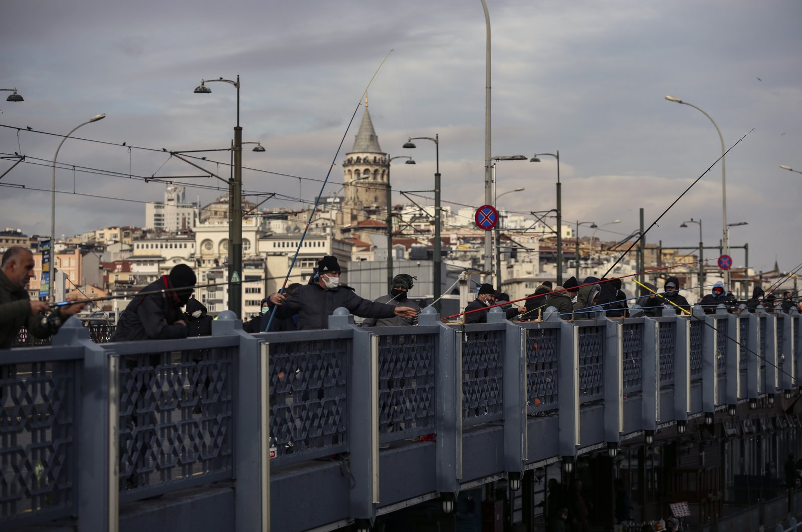 Fishermen wearing masks to help protect against the spread of coronavirus, fish off the Galata Bridge hours before a two-day weekend lockdown, in Istanbul, Friday, Jan. 29, 2021. (AP Photo)