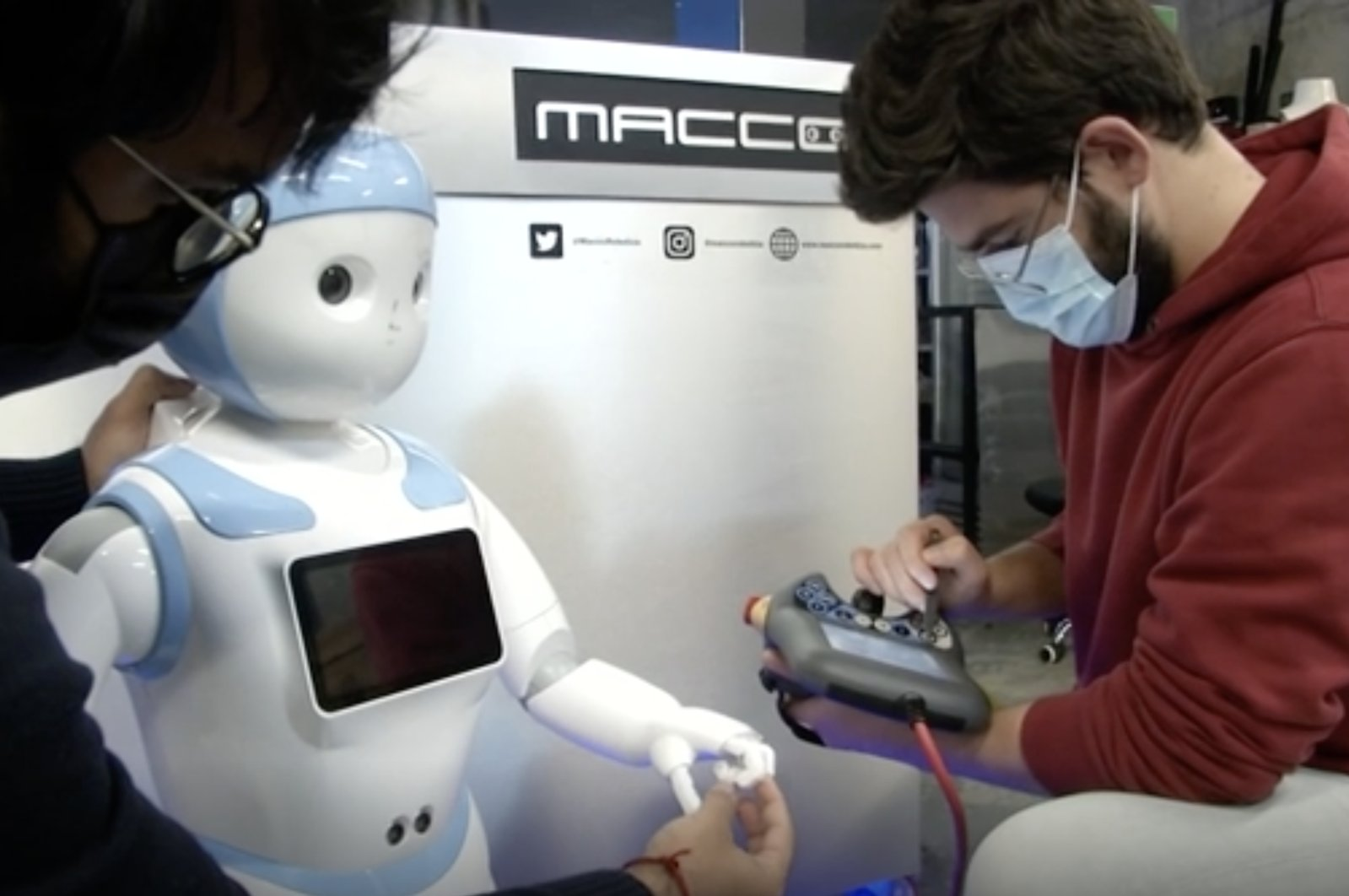 A still image from a video shows Kishhanth Renganathan, Chief Technology Officer (CTO) of Macco Robotics, and another engineer working on a human-like robot in a workshop, Seville, Spain. (AP Photo)