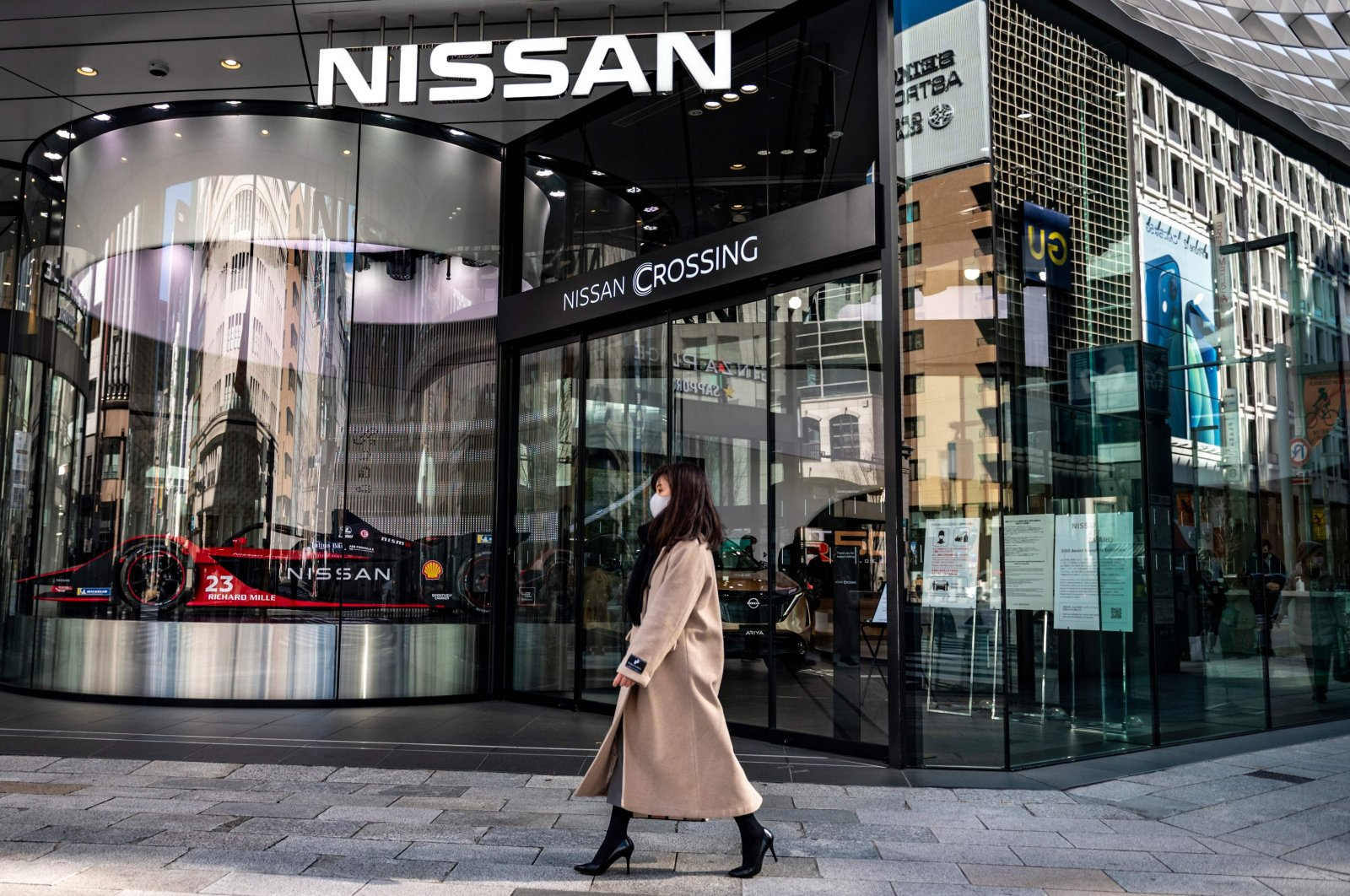A woman walks past a Nissan showroom in the Ginza district of Tokyo, Feb. 9, 2021. (AFP Photo)