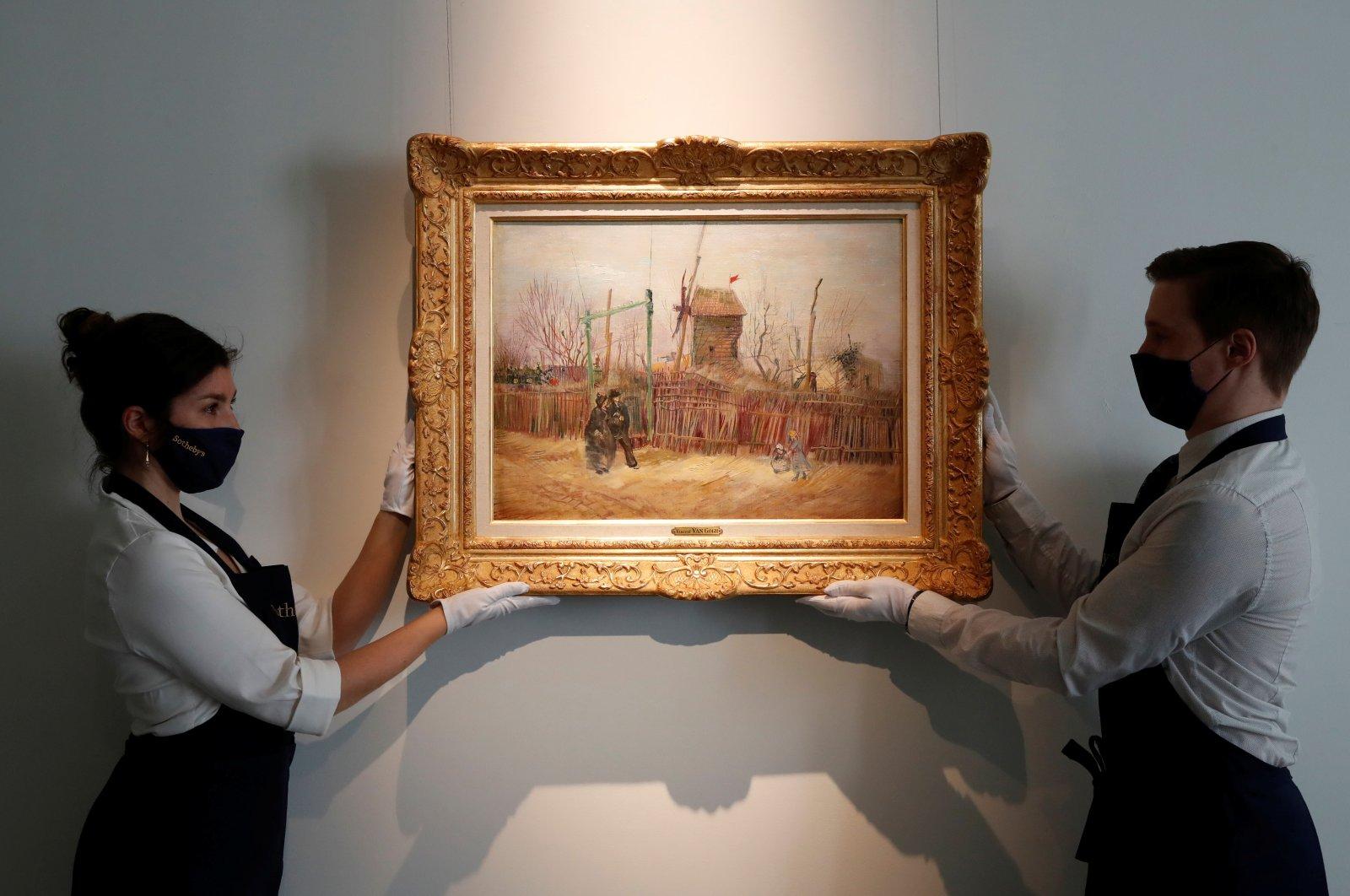 "Sotheby's Paris employees pose with the 1887 painting of a Paris street scene ""Scene de rue a Montmartre"" by the Dutch painter Vincent Van Gogh, France, Feb. 24, 2021. (REUTERS PHOTO)"