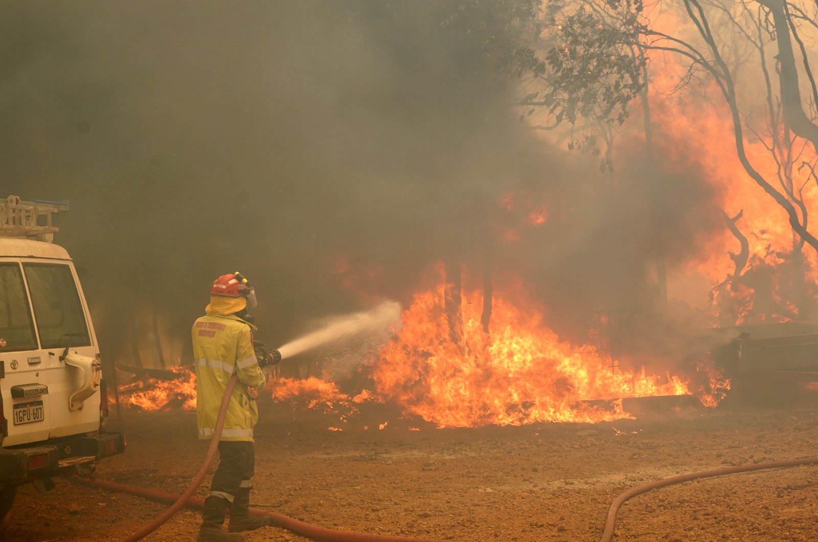 In this photo provided by the Department of Fire and Emergency Services, a firefighter attends to a fire near Wooroloo, northeast of Perth, Australia, Feb. 2, 2021. (AP Photo)
