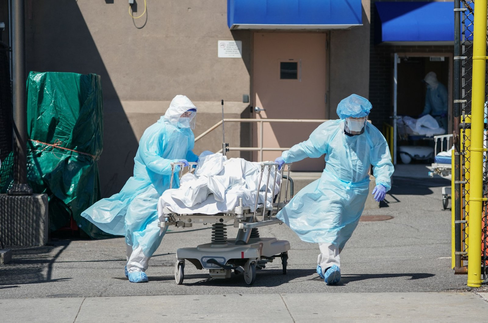 In this file photo, bodies are moved to a refrigeration truck serving as a temporary morgue at Wyckoff Hospital in the Borough of Brooklyn in New York on April 6, 2020. (AFP Photo)