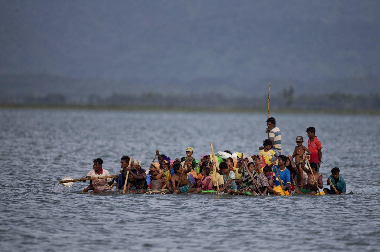 Rohingya Muslims use a makeshift raft made with plastic containers to cross the Naf river from Myanmar into Bangladesh, near Shah Porir Dwip, Bangladesh, Nov. 12, 2017. (AP Photo)