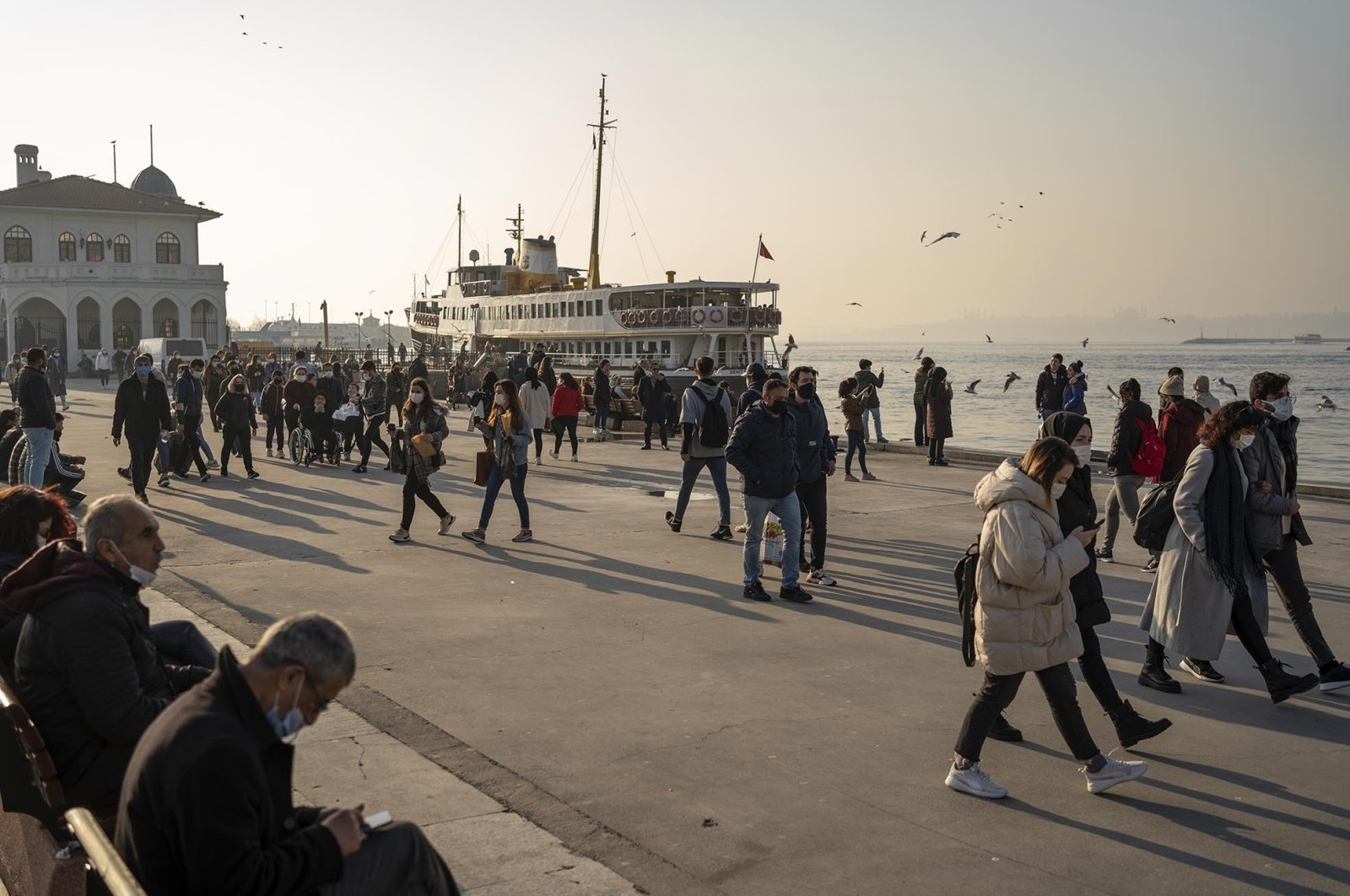 People wearing protective masks against the coronavirus spread walk by the seaside in Kadıköy district, Istanbul, Turkey, Feb. 23, 2021. (Photo by Getty Images)