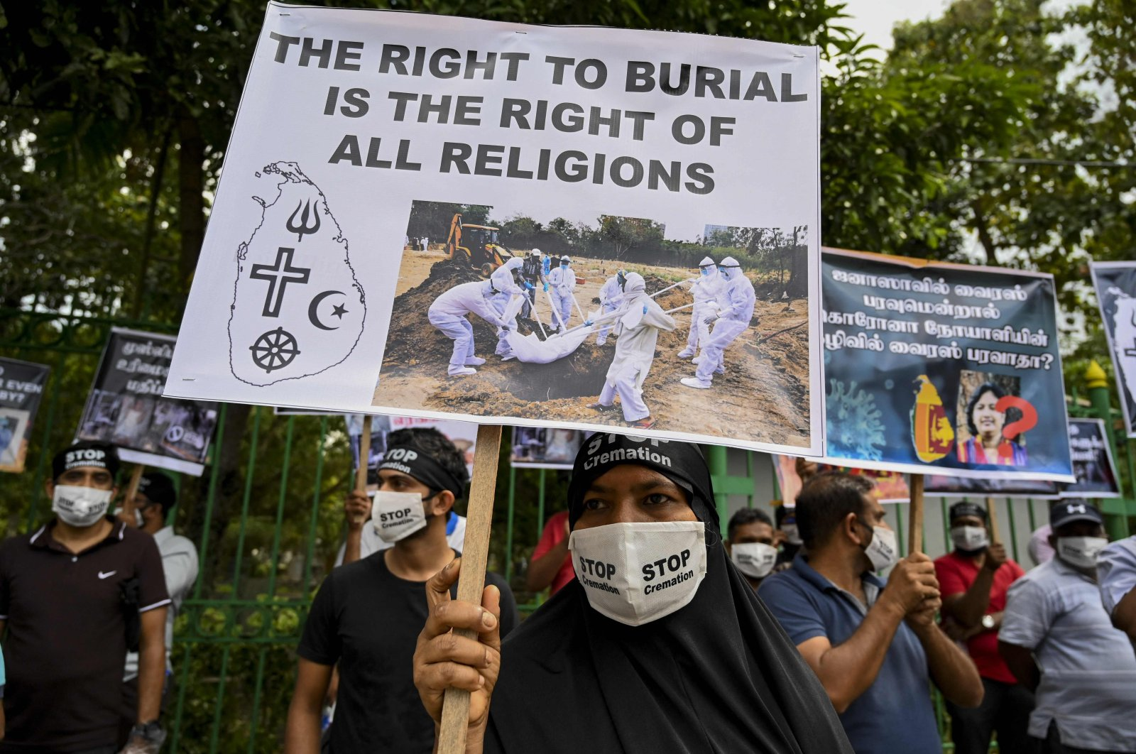 Protesters hold placards during a demonstration against the government policy of forced cremations of Muslims who died of the coronavirus, outside a cemetery in Colombo, Dec. 31, 2020. (AFP Photo)