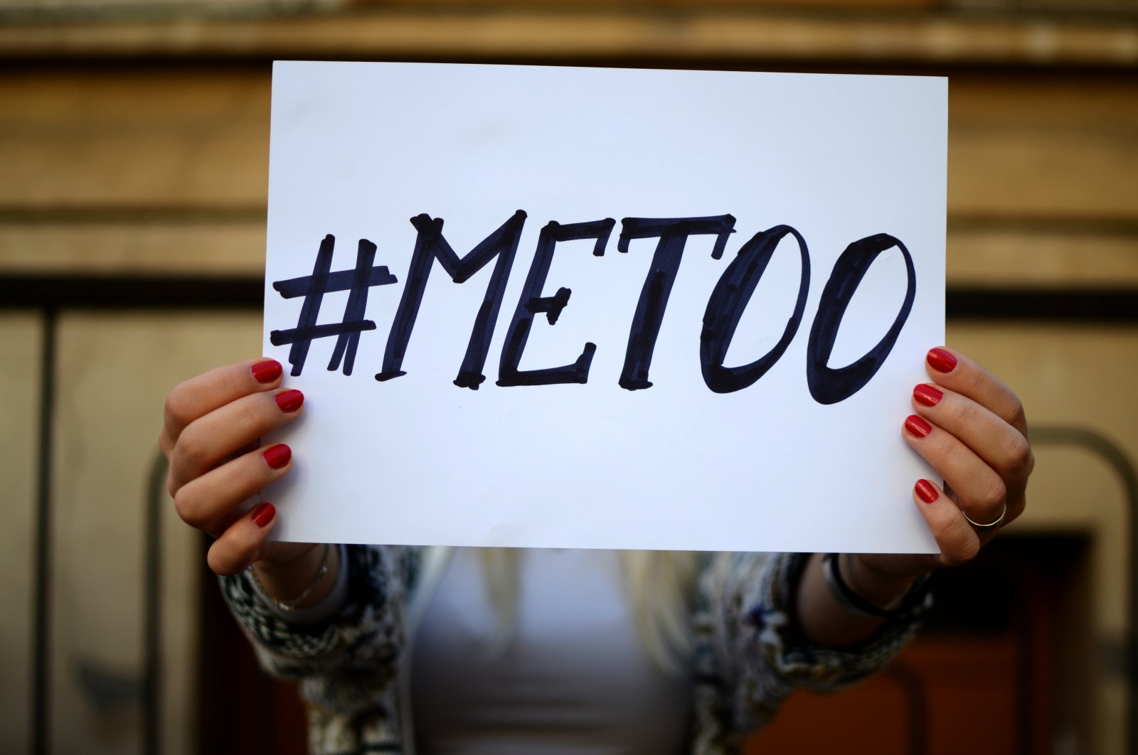 """A woman holds up a sign that says """"#METOO."""" (Shutterstock Photo)"""