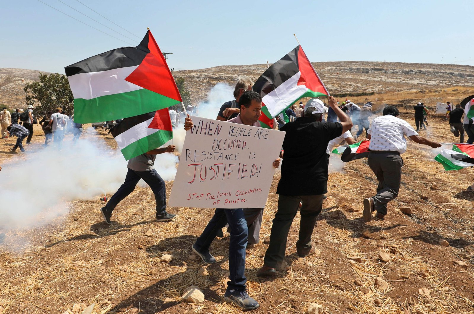 Palestinian protesters run from tear gas canisters fired by Israeli troops during clashes following a demonstration against the expropriation of Palestinian land by Israel, in the village of Kafr Malik northeast of Ramallah in the Israeli-occupied West Bank on Sept. 13, 2019. (AFP Photo)