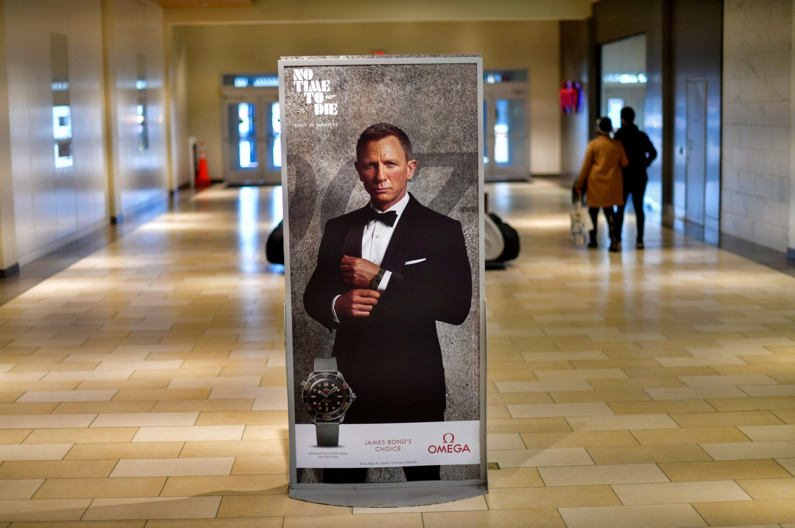 """Shoppers walk past an advertisement for the upcoming James Bond film """"No Time to Die"""" at the Christiana Mall in Newark, Delaware U.S. Nov. 19, 2020. (Reuters Photo)"""