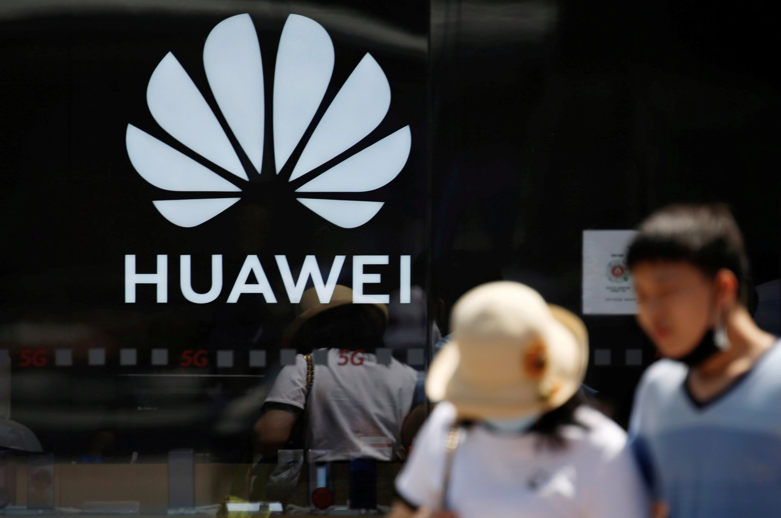 People walk past a Huawei logo on the facade of its store at a shopping complex in Beijing, China July 14, 2020. (Reuters Photo)