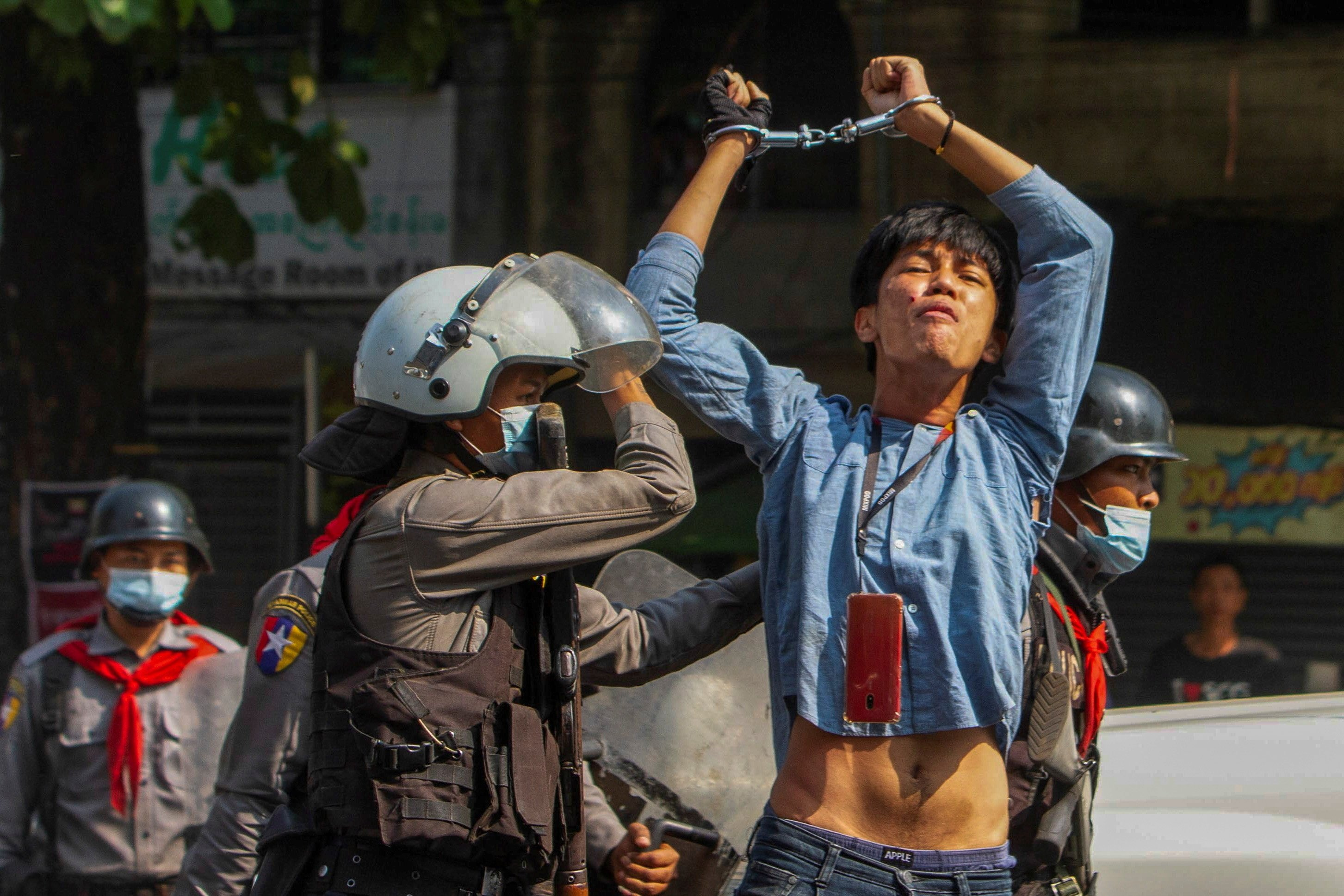 A pro-democracy protester is detained by riot police officers during a rally against the military coup in Yangon, Myanmar, Feb. 27, 2021. (Photo: Reuters/Stringer)