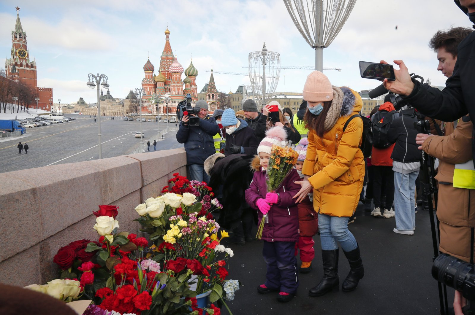 A woman with her children lays flowers near the spot where Russian opposition leader Boris Nemtsov was gunned down, in Moscow, Russia, Feb. 27, 2021. (AP Photo)