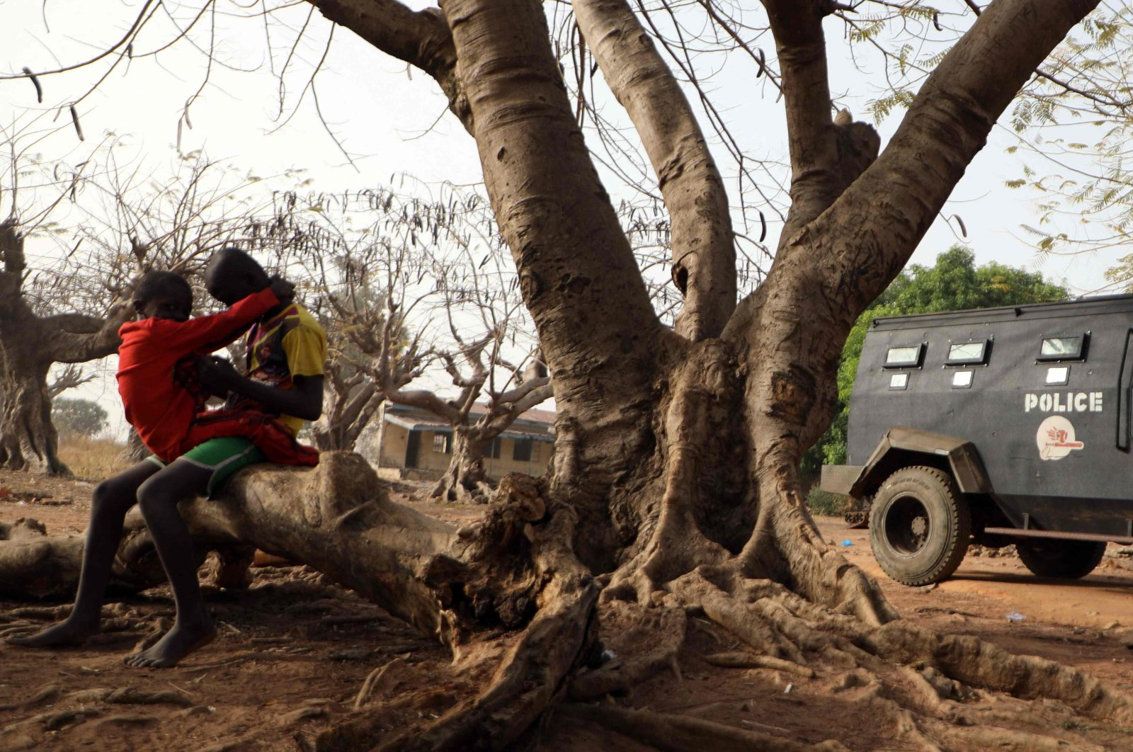 Children sit on a tree trunk next to an armoured personnel carrier stationed inside the Government Science College where gunmen kidnapped dozens of students and staffs, in Kagara, Rafi Local Government Niger State, Nigeria, Feb. 18, 2021 (Photo by Kola Sulaimon / AFP)